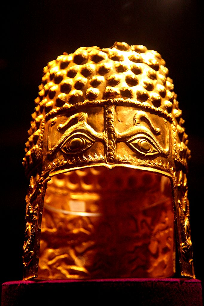Solid gold helm made around end of 5th – beginning of 4th century B.C. by Thracian tribes (Geto-Dacians). Likely part of the martial display regalia of a king or a powerful warlord. It is a studded cylindrical helmet (missing top, otherwise intact)  Decorations are mystical sacrificial images with ancient Oriental elements, of Scythian influence.  Helm created by repeatedly hammering a very thick sheet of gold on a wooden support.  25cm tall, 770g.