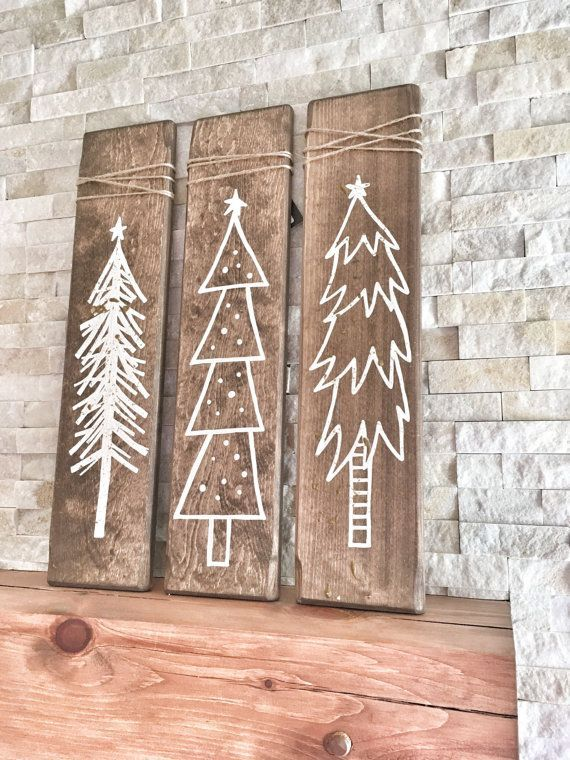 These Rustic Wooden Christmas Trees are a unique piece for your home during the holiday season! This listing is for a set of three hand painted white Christmas trees on walnut stained wood pieces and two pieces are sprinkled with gold glitter for a little sparkle :) The wood has been sanded smooth, stained, painted & distressed by hand for that perfect rustic touch Measurements: each piece of wood is 24 x 5.5 Each wooden tree has a brass plated tooth hanger on the back for easy hanging! *...