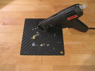 Rest your hot glue gun on a silicone pot holder. It will protect your surface AND the glue globs will slide right off. Hullo!