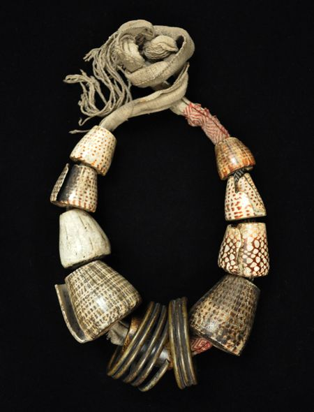 "Akusan (woman's belt)  Bontoc, Philippines   Conus shells, coiled brass, woven cotton fabric, human bone  35"" (89 cm) long, as tied, largest conus shell is 2-1/2"" (6.5 cm) long  Early 20th century"