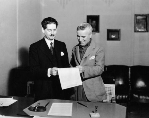"""chaplinfanage: """"  Charlie Chaplin signing contract for the first showing of Modern Times (1936) at the Trivoli theatre in London with arthur Jarratt.  """""""