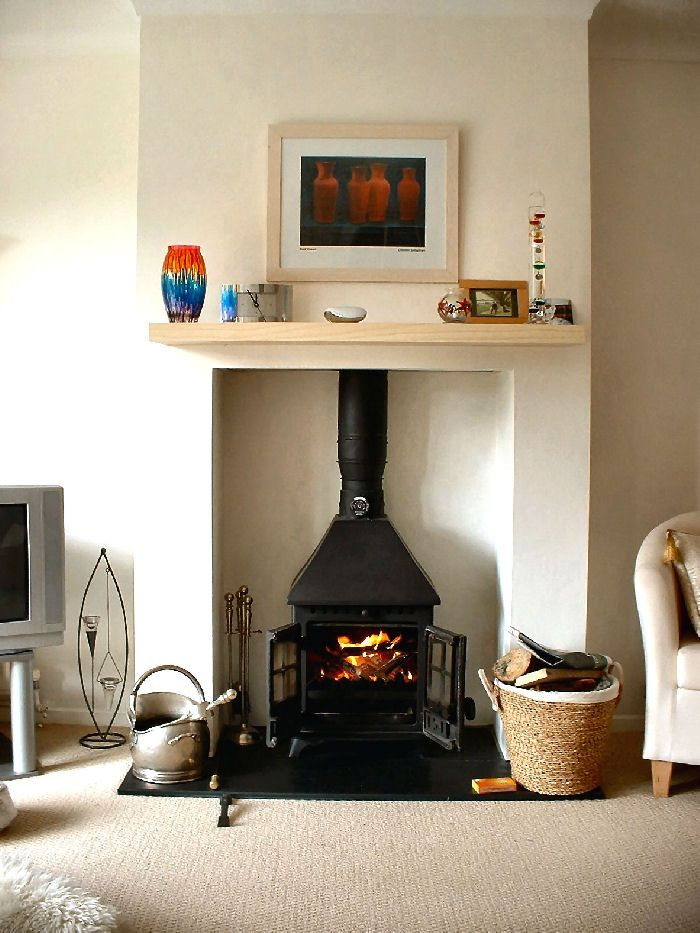 Yeoman wood burning stove in a simple fireplace.