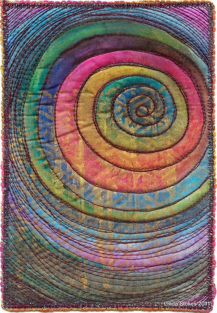 Spiral quilt by lyndy laurel ~ Water soluble pencils & crayons on cotton. gold roller print over the top. Quilted with variegated cotton thread. edged with yarn. art quilt.