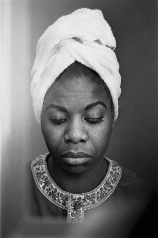 """A reflection of Nina Simone in a motel room mirror in Buffalo, New York. Photograph by © Alfred Wertheimer, 1964."""