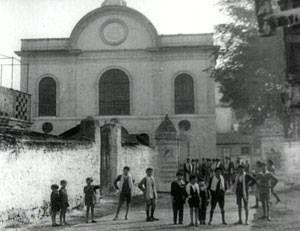 H μητροπολιτική συναγωγή της Θεσσαλονίκης Μπεθ Σαούλ στην γωνία Β.Ολγας με Παρασκευοπούλου. Ενδιαφέρουσα λεπτομέρεια τα παιδάκια που μάλλον φοράνε ταλέτ, (ταλέτ είναι η εσάρπα που φοράνε ως εξάρτημα στην προσευχή).