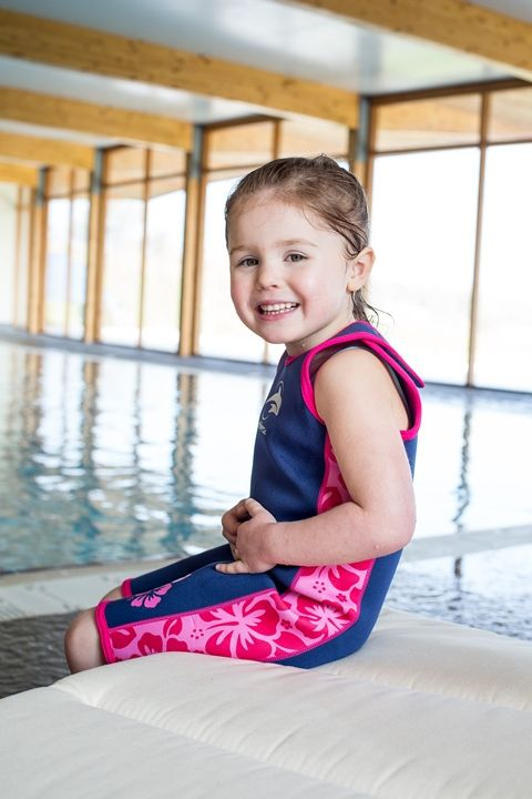Gorgeous girl showing off the Konfidence neoprene Warma Wetsuit - designed for infants and older children aged up to 7 years who feel the cold in the pool or on the beach.