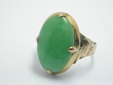 One yellow gold ring with foliate motif shoulders. One oval cabochon jadeite jade (2.05 carats: natural medium green colour).