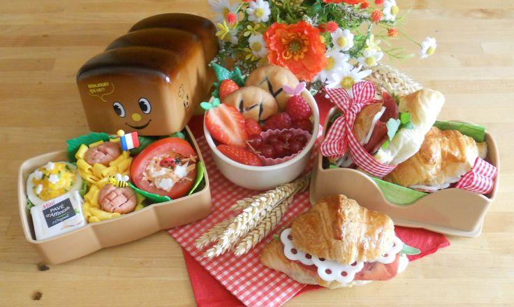 """8_Lise-Marie_France Le """"Croissandwich Bento"""" vous invite au cœur de la France. Mon pays... Même le bento, en forme de brioche, participe au thème du moment. Des sandwiches à base de croissants, garnis de jambon de pays, de fromage de chèvre, et de roquette fraîche. En accompagnement : un œuf mimosa, deux tournesols saucisses/omelette, un panier-tomate garni de crudités, avec un petit fromage. Un dessert: fraises Garriguette, framboises, groseilles, et sablés à la framboise."""