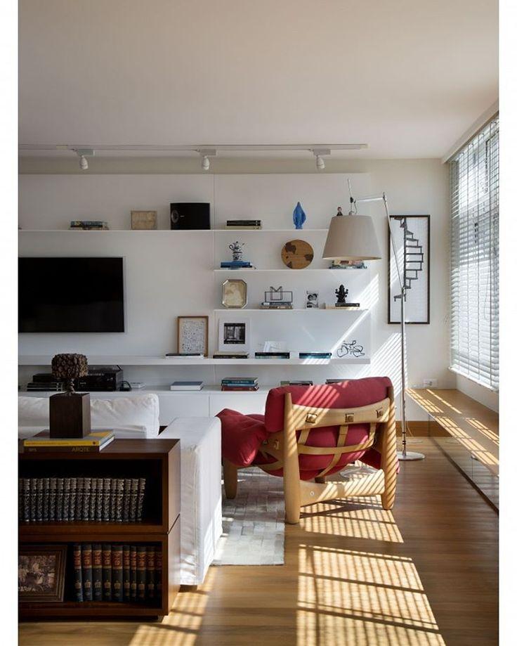 #olhomágicocj #mourafariamambriniarquitetura Destacamos na sala de estar deste apartamento a poltrona Mole, assinada por Sergio Rodrigues. Reparem que a peça ficou mais contemporânea com o estofamento de linho vermelho. O móvel modulado para livros apoiado no chão, foi posicionado atrás do sofá. Na parede, a estante de laca brilho com prateleiras de aço foi desenhada pelo nosso escritório. FotoMCA Estudio/Divulgação @mourafariamambriniarquitetura#décor #decoração #decoration #homedecor…