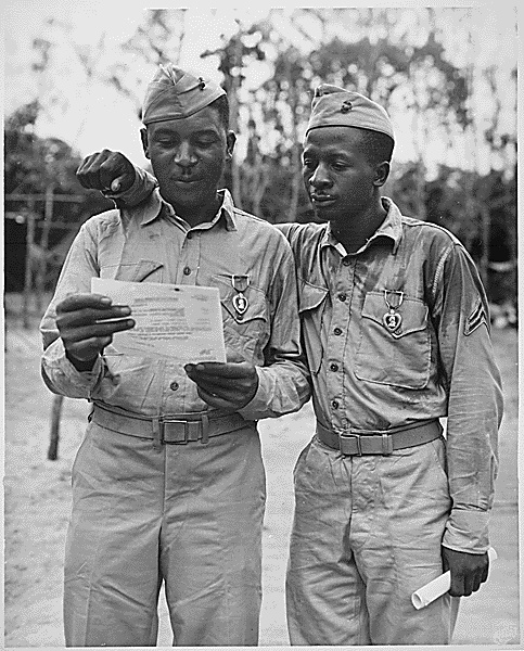 Pictured are Staff Sergeant Timerlate Kirven and Corporal Samuel J. Love, two African American Marines of the famed Second Marine Division, wearing their Purple Hearts for wounds received in the Battle of Saipan.