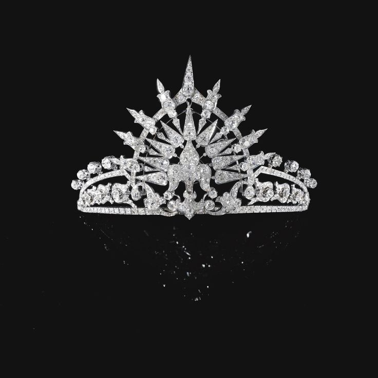 Diamond tiara, circa 1900    Estimate: 100,000 - 150,000 CHF  The central fleur-de-lys motif set en tremblant to a tiara composed of foliate and lanceolated motifs, set with cushion-shaped, circular-cut and rose diamonds, inner circumference approximately 170mm, accompanied by a detachable tiara frame, inner circumference approximately 340mm