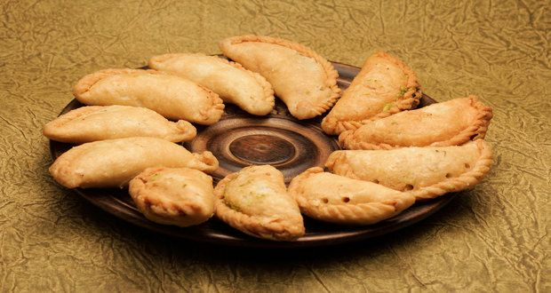 Coconut Gujiya Recipe - Holi celebrations are incomplete without this traditional sweet. Khoya, mava, coconut and pistachio stuffed in maida pockets, fried and dipped in sugar syrup. Coconut gives this festive classic an interesting twist. This type of gujiya is also known as in Maharashtra. You can even decide to bake these gujiyas if you are conscious about your health.