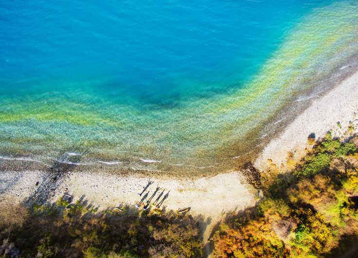 Taking a hike along the beach near Glenorchy (maybe you can see our long shadows!). When we got the quadcopter up we were surprised to see all the colors in the shoreline. #Glenorchy