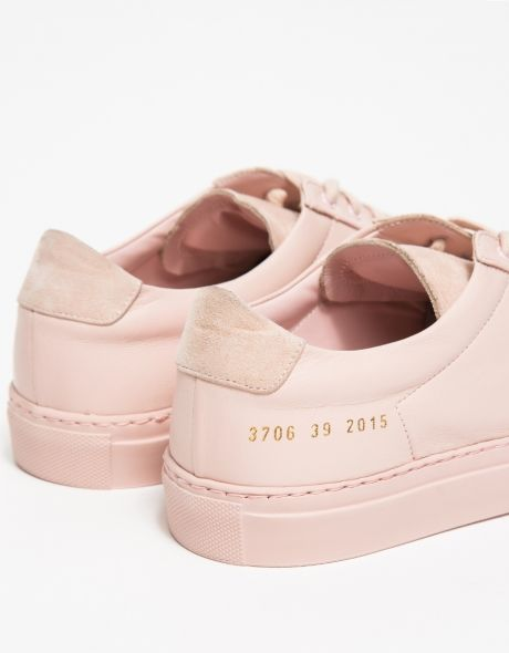 From Woman by Common Projects, a classic leather low top sneaker in blush. Features round toe, smooth leather and suede uppers, leather lining, matching eyelets, gold heat pressed serial number detail on heel, extra set of blush laces and blush rubber sol