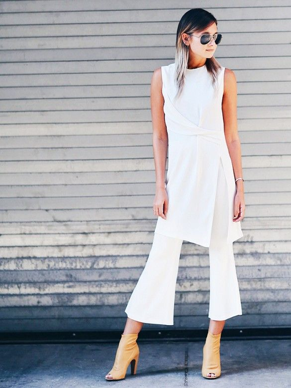 A white sleeveless tunic is worn with flared white pants, tan peep-toe booties, aviators and simple silver bracelet.