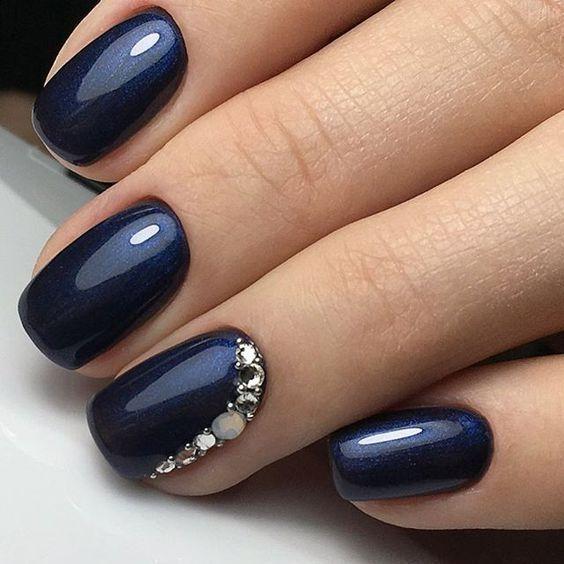 Auch mit kleinen Schmucksteinen kann man ein Nagel-Design stilvoll aufwerten. Der Glanz des dunkelblauen Nagellacks wird durch die funkelnden Steine n…