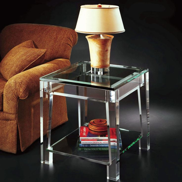 fancy tiny glass table with very long legs and there good drawer with lights sitting pretty on top