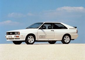 Audi Quattro. The European model was ultimately equipped in 1989 with a 2.2L 20-valve DOHC turbocharged inline 5 producing a potent (well, for the 80's, anyway) 217bhp – with power going to all 4 wheels. The Quattro could reach a top speed of 143 mph and had force choke-like grip to ensure quick entry and exits in corners. Sadly, the North American models were nerfed due to emissions regulations, and so buyers would want a Euro-spec or a tuned up domestic model