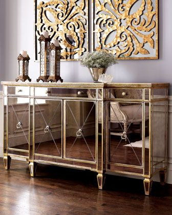 """Amelie"" Mirrored Buffet/Console - Neiman Marcus $1599 off 2129.  Dressed in beveled, antiqued-mirror veneers, this reflective console showcases your home and opens the space as it adds functionality with multiple storage options. Made of hardwoods and mirrored veneers. Finished in silver leaf with golden antiqued-glaze highlights. Three drawers and four doors. 70""W x 20""D x 38""T."