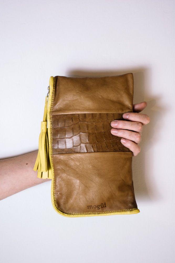 Cartera de mano, exterior en cuero marrón con diferentes texturas y detalles en cuero amarillo. Forro estampado con bolsillo interior.Medidas 16x26cm.Hecha a mano.