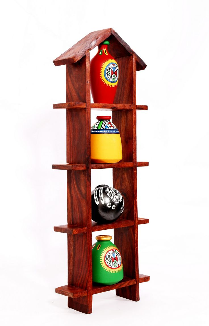 House shaped wall unit frame in sheesham wood. With set of four warli painted miniature pots. Will add colour and life to your walls. A classy yet ethnic piece of art.  (There may be very MINOR VARIATIONS in color combinations and figure designs, between displayed and dispatched products, due to variety of artisans who handcraft the products. The look, feel and quality will , however, be consistent with what you see. That is an Indikala promise).