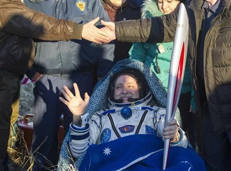 Cosmonaut Fyodor Yurchikhin holds the torch of the 2014 Sochi Winter Olympic Games after landing near the town of Zhezkazgan in central Kazakhstan 11/11/2013