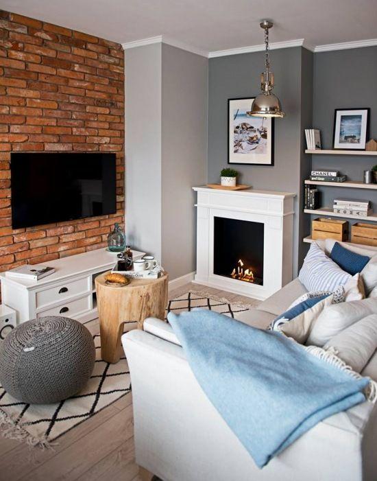 Ciekawa i przytulna aranżacja salonu, w którym ciepły charakter potęguje kominek. Czerwone cegły przyczyniają się do oryginalnego wyglądu wnętrza, a wiele ozdób i dodatków nadaje mu osobisty charakter. Błękitne i niebieskie detale nawiązują do nadmorskiego klimatu, jaki przewodzi aranżacji całego mieszkania.