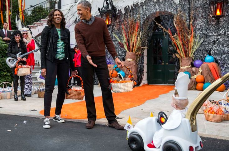 The Obamas react to a child in a pope costume and mini popemobile as they welcomed children during a Halloween event on the South Lawn of the White House.