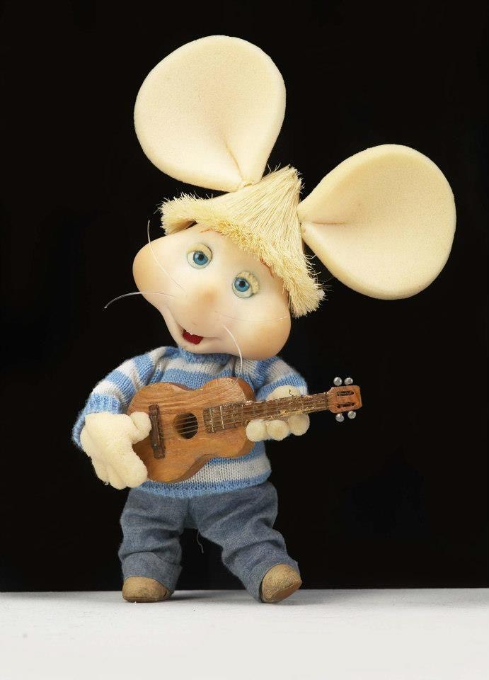 Topo Gigio strums his guitar for you.