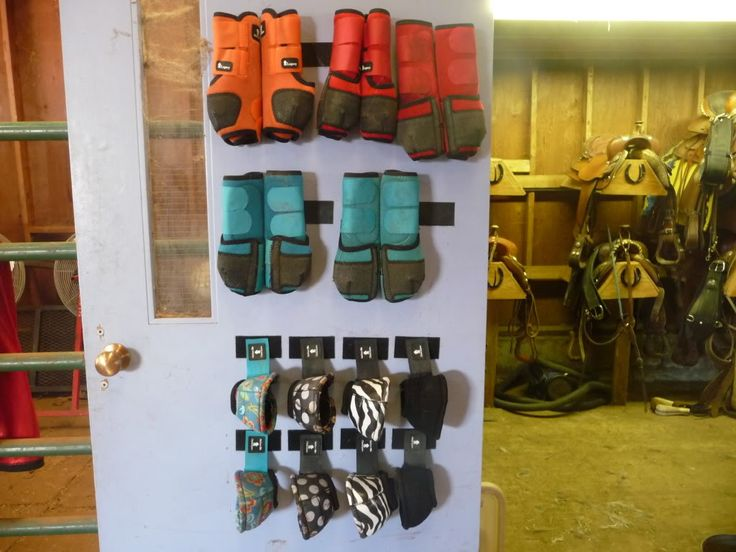 Boots hung by velcro strips on a wall. Great idea for tack room organization.