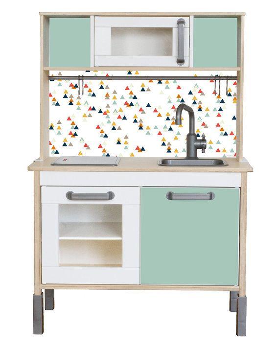 +Möbelfolie TRIANGLIG passend zur IKEA DUKTIG Kinderküche - Farbe Mint+ Deine Ikea Kinderküche DUKTIG ist noch weiß? Dann solltest du wissen, dass warme Farben das kreative Spielen fördern. Damit du nicht zu Pinsel und Lack greifen musst, kannst du sie mit Möbelfolie aufwerten. Diese lässt sich später wieder rückstandfrei ablösen. Die Möbelfolien gibt es in 18 verschiedenen Outfits! Die IKEA Kinderküche hat keine Rückwand, so dass die Dekorationsfolie für den Spritzschutz an der Wand…