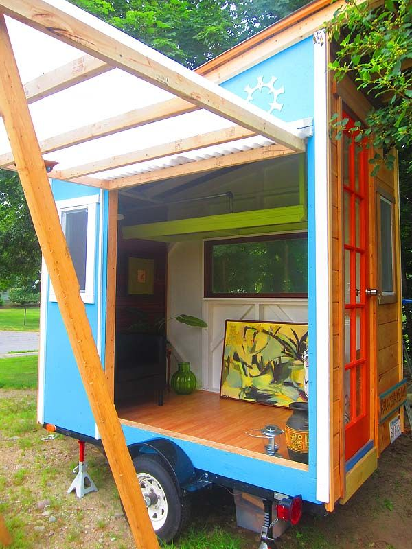 tiny house on wheels has a pop-out window that acts as  an awning.