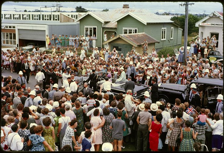 Description 35mm colour slide showing the Queen in an open top car (Ford Galaxie Convertible) surrounded by crowds during her visit to the Crown Lynn Pottery on Totara Avenue, New Lynn