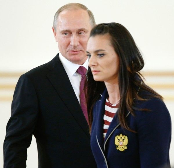 Vladimir Putin Photos Photos - Russian President Vladimir Putin reacts as Russia's pole vaulter Yelena Isinbayeva passes by him during a reception in honour of members of the country's Olympic team departing for the Rio Games at the Kremlin in Moscow on July 27, 2016..President Vladimir Putin on July 27 said the absence of some Russian stars at the Rio Games would hit the quality of the competition. / AFP / POOL / Alexander Zemlianichenko - Vladimir Putin Meets Russian National Olympic Team