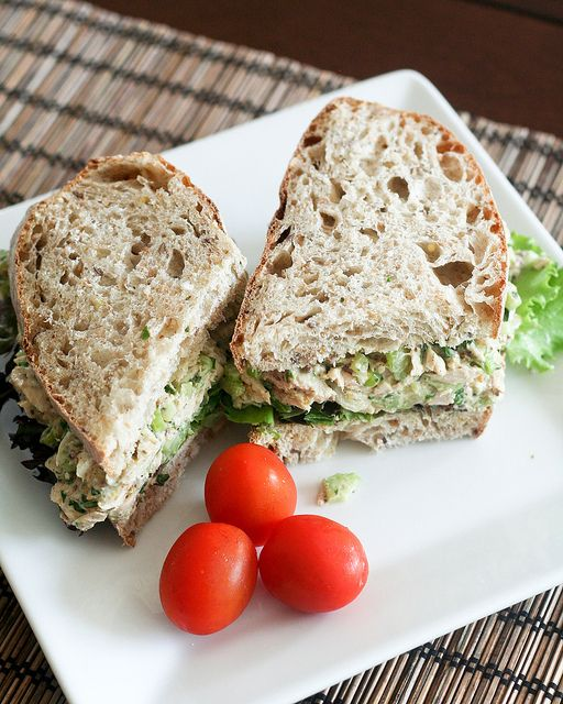 Tuna sandwich   ¼ cup 0% fat greek plain yogurt  1 tsp Dijon Mustard  1 tbsp Old Style whole grain mustard  ¼ tsp black pepper  1 celery rib, finely chopped  1 green onion, finely chopped  1 pinch cayenne pepper  1 tsp lemon juice  1 can chunk light tuna fish, in water  2 slices whole grain bread of your choice  a handful of leafy greens