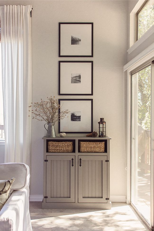 Three small black and white photographs are framed in large white mounts and slim black frames over a cabinet, adding a homely touch.