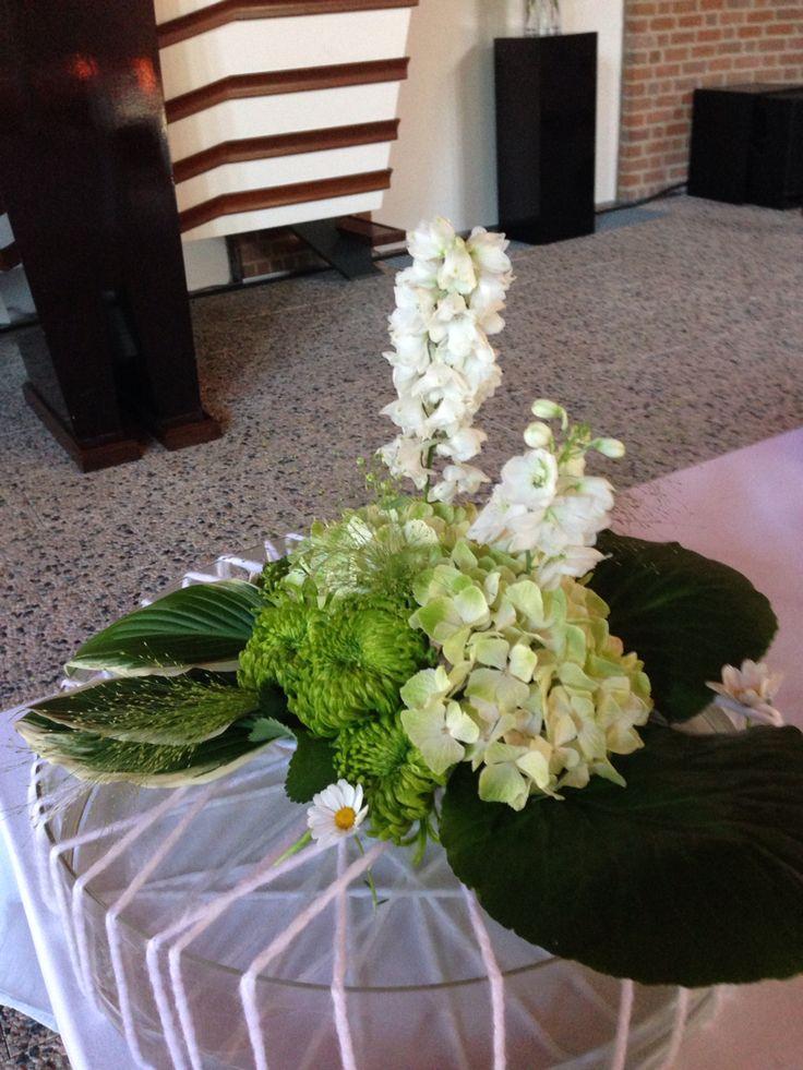 Avondmaal Een schaal van 10 centimeter hoog omwikkeld met wol. In de gaten die ontstaan de bloemen gestoken. Hortensia, chrysanten, Panicum, Bergenia blad en Hosta blad