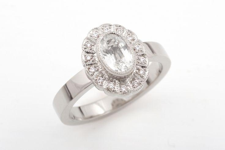 Grace-sormus valkokultaa. Kivinä väritön safiiri ja timantit.