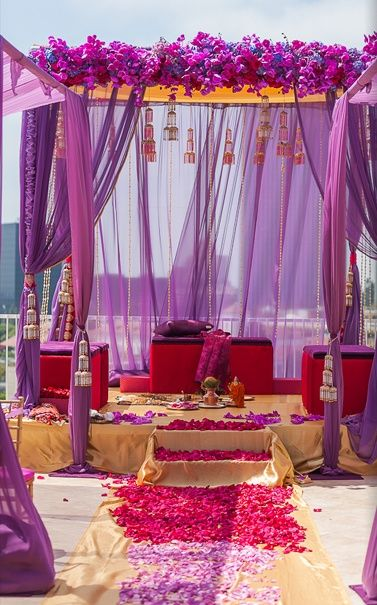 The purple fabric mandap is all set and ready to make for a royal wedding. Flowered Mandap, indian wedding decor, indian mandap, indian wedding #IndianWedding