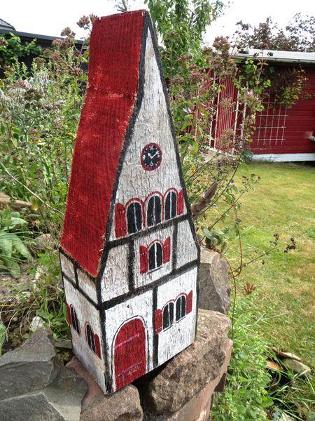 Holzhaus von Claudias-Art auf DaWanda.comDieses Haus ist mit seiner ungewöhnlichen Form ein Hingucker in jedem Garten oder Wohnraum.Es wurde aus einem alten Holzbalken gefertigt. Das Haus ist handbemalt und ein Unikat.Das Haus hat einen ganz eigenen Charakter mit der Uhr und dem großen Dach.