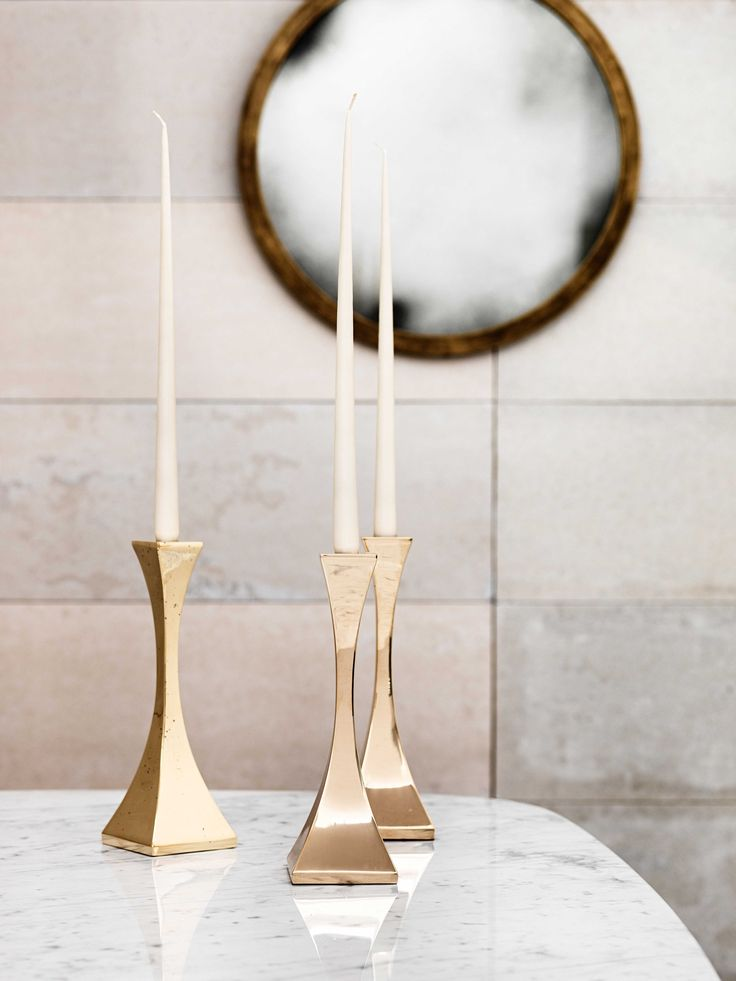 Polished Bronze Capricorn candlesticks and a Madison round mirror with an Antique Bronze finish.