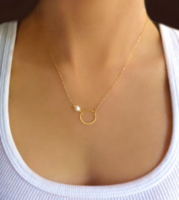 "This minimalist and feminine necklace features a 17mm gold vermeil circle eternity link and is joined with one 5-6 mm genuine and natural freshwater pearl. Necklace is shown at a length of 18"" but is available in multiple lengths. Chain is available in both sterling silver or 14k gold filled - just choose during check out. Necklace closes with a 14K gold filled or sterling clasp. This symbolic necklace makes for the perfect gift! All Jewelry is carefully packaged for a safe..."