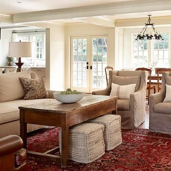 Color scheme with red/plaid accents. brown book shelves. white/cream/taupe sofas. thistle rug.
