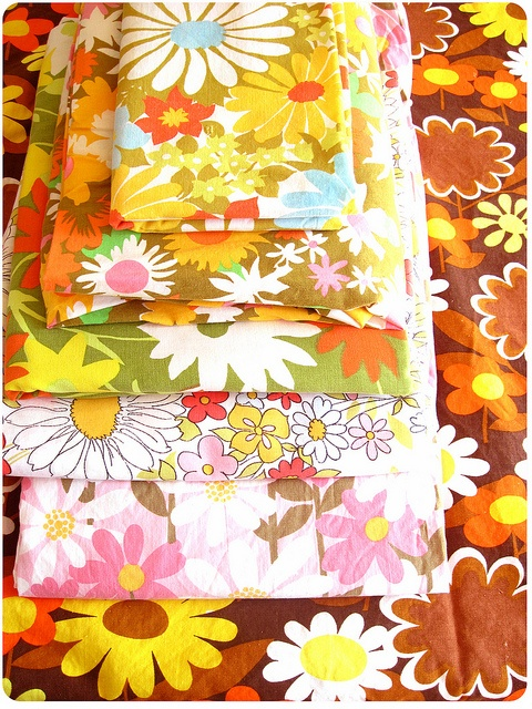 I have a pillow made out of some vintage fabric.  The pillow's pattern is like the brown flowered pattern on the bottom of this pile.  My mother made the pillow for me b/c I loved the pattern & colors.