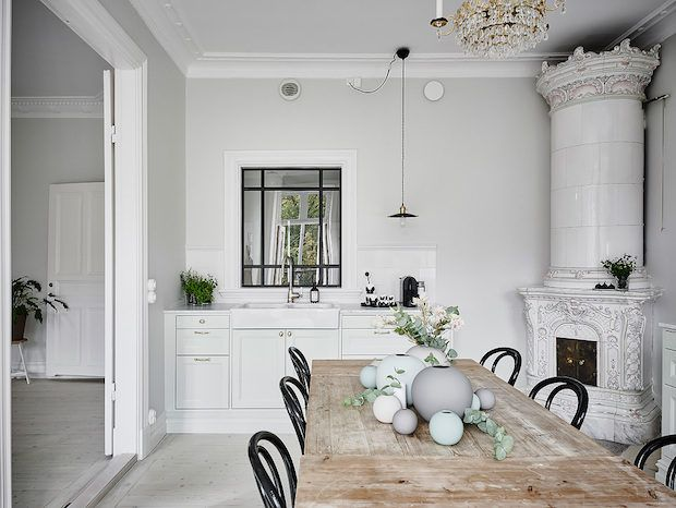 A 'kakelugn' masonry oven, wooden table and window with black frames in a beautiful Swedish home in calm, muted tones. Entrance, Anders Bergstedt.