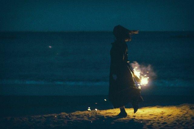 夜の浜辺で手持ち花火と女性のシルエット のフリー素材 photo outdoor celestial