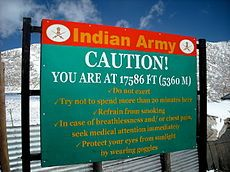 "Sign displays ""Caution! Your are at 17586 ft (5360 m)""  ""Altitude sickness—also known as acute mountain sickness (AMS), altitude illness, hypobaropathy, ""the altitude bends"", or soroche—is a pathological effect of high altitude on humans, caused by acute exposure to low partial pressure of oxygen at high altitude. It commonly occurs above 2,400 metres (8,000 feet).[1][2] It presents as a collection of nonspecific symptoms, acquired at high altitude or in low air pressure, resembling a case…"