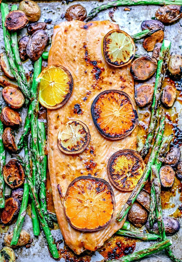 This Easy Honey Citrus Sheet Pan Salmon is slathered with a finger-licking honey citrus glaze and baked alongside crisped up potatoes + asparagus for an easy weeknight one-pan dinner. #weeknightdinner #easyrecipes #salmon #sheetpan #dinner #onepan #healthyfood #healthyrecipes #citrus #fish #seafood #pescetarian #pescatarian