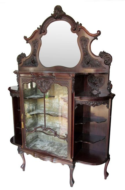 An English Carved Mahogany Display Cabinet with Cabriolet Legs, Carved Foliate Detail, Scalloped Side Shelves, and Felt Lined Wood Shelves.