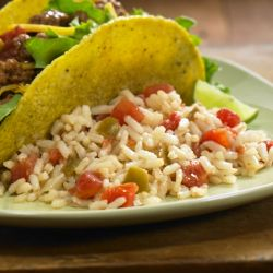 A Spanish rice recipe starts with instant rice, tomatoes and onions combined with chili powder and cumin for an easy side dish